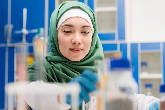 Vista frontal do cientista feminina com hijab no laboratório