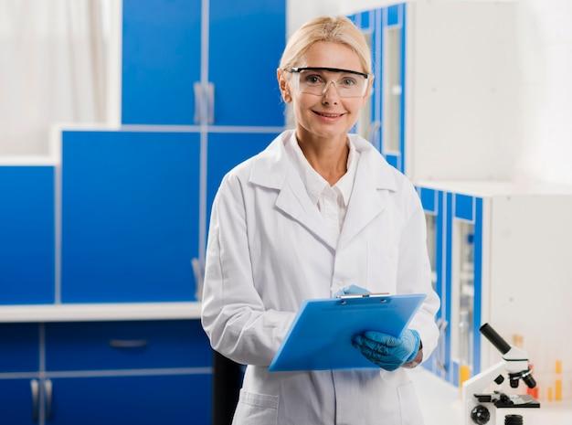 Vista frontal do cientista feminina com luvas cirúrgicas e bloco de notas posando no laboratório