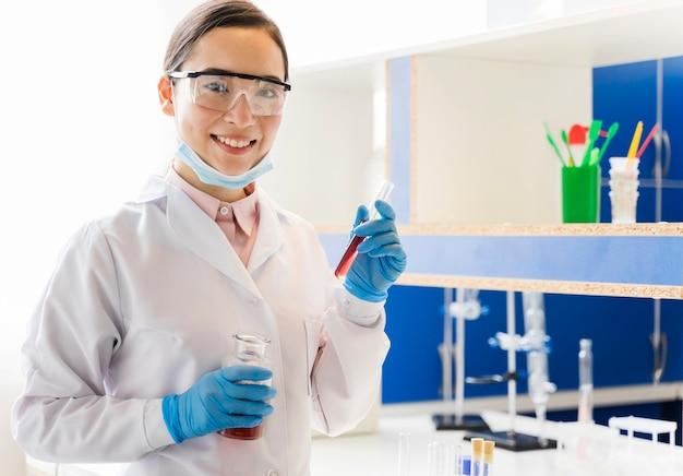 Vista frontal do cientista feminina com luvas cirúrgicas posando no laboratório