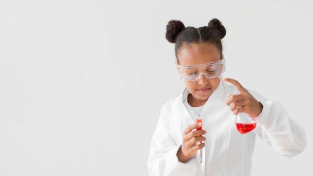 Vista frontal do cientista garota com jaleco e óculos de segurança