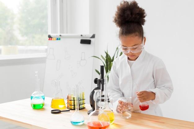 Vista frontal do cientista garota experimentando poções