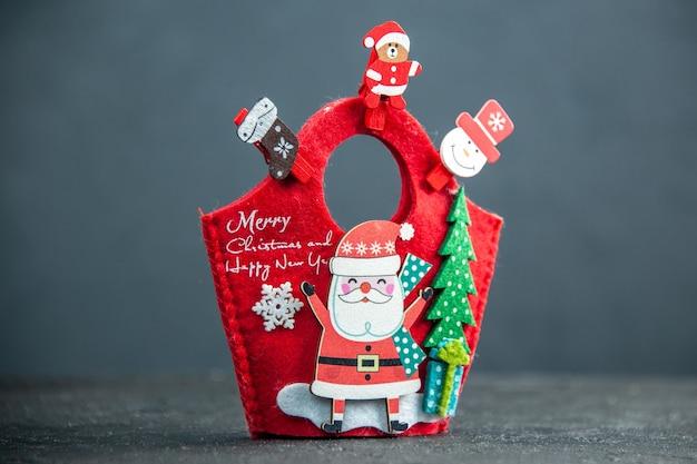 Vista frontal do clima de natal com acessórios de decoração e caixa de presente de ano novo na superfície escura