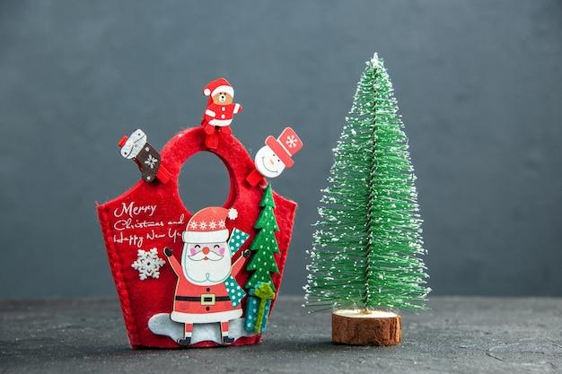 Vista frontal do clima de natal com acessórios de decoração na caixa de presente de ano novo e a árvore de natal na superfície escura