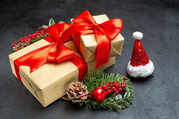 Vista frontal do clima de natal com lindos presentes com fita em forma de arco e acessórios de decoração de ramos de abeto chapéu de papai noel cones de conífera em um fundo escuro