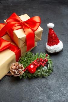 Vista frontal do clima de natal com lindos presentes com fita em forma de arco e acessórios de decoração de ramos de abeto chapéu de papai noel cones de coníferas em fundo escuro