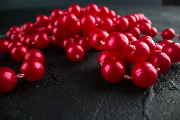 Vista frontal do colar vermelho sobre fundo escuro. foto colorida com frutas vermelhas