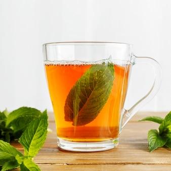 Vista frontal do conceito de chá de ervas na mesa de madeira