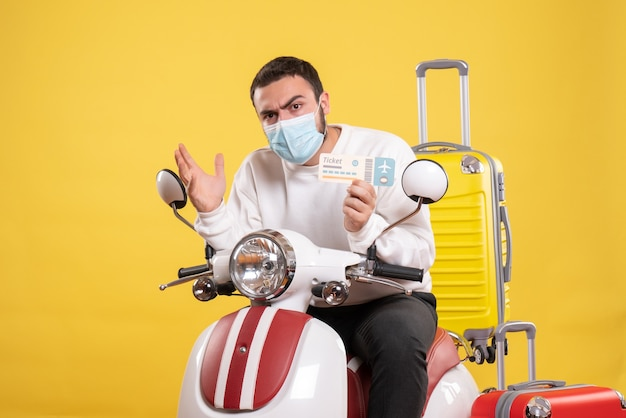Vista frontal do conceito de viagem com um cara jovem pensando numa máscara médica sentado na motocicleta com uma mala amarela e segurando o bilhete
