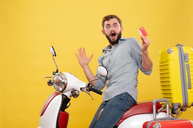 Vista frontal do conceito de viagens com jovem emocional surpreso sentado na moto com as malas segurando o cartão do banco em amarelo