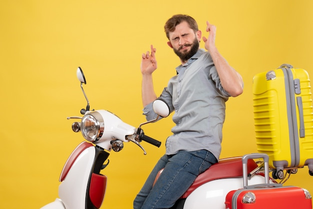 Vista frontal do conceito de viagens com um jovem barbudo sentado na motocicleta com malas sonhando cruzando os dedos fechando os olhos sobre ele no amarelo