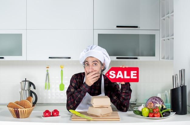 Vista frontal do confuso chef masculino de uniforme segurando uma placa vermelha de venda e colocando a mão na boca na cozinha moderna