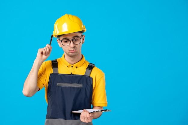 Vista frontal do construtor masculino de uniforme com a nota do arquivo nas mãos na parede azul