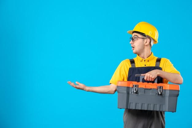Vista frontal do construtor masculino de uniforme com caixa de ferramentas na parede azul