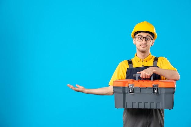 Vista frontal do construtor masculino de uniforme com caixa de ferramentas nas mãos na parede azul