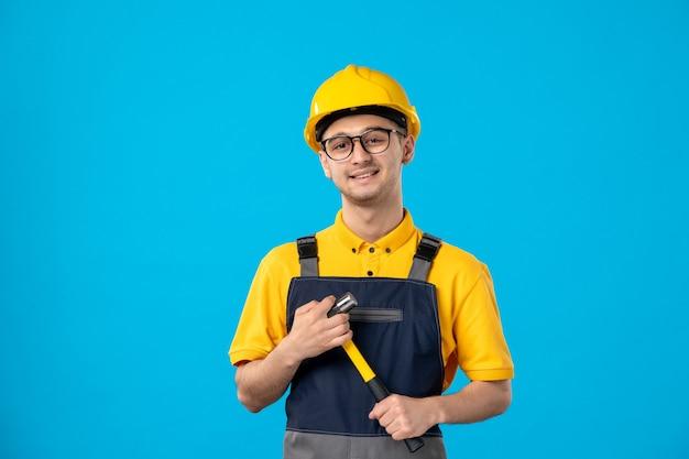 Vista frontal do construtor masculino de uniforme com o martelo nas mãos na parede azul