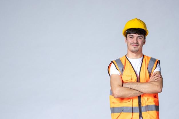 Vista frontal do construtor masculino de uniforme e capacete amarelo na parede branca