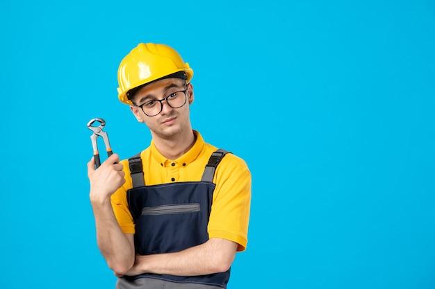 Vista frontal do construtor masculino de uniforme e capacete com alicate na parede azul