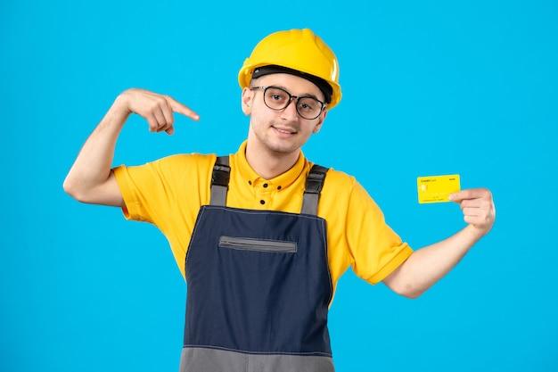 Vista frontal do construtor masculino de uniforme e capacete com cartão de crédito na parede azul