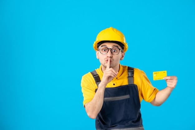 Vista frontal do construtor masculino de uniforme e capacete com cartão de crédito pedindo silêncio na parede azul