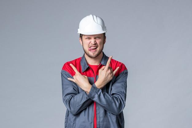 Vista frontal do construtor masculino de uniforme e capacete em fundo cinza