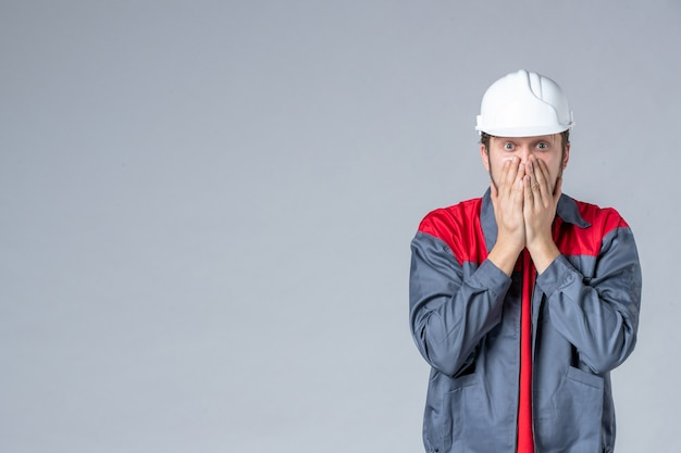 Vista frontal do construtor masculino de uniforme e capacete em fundo claro