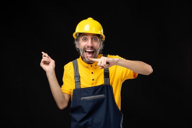 Vista frontal do construtor masculino de uniforme na parede preta