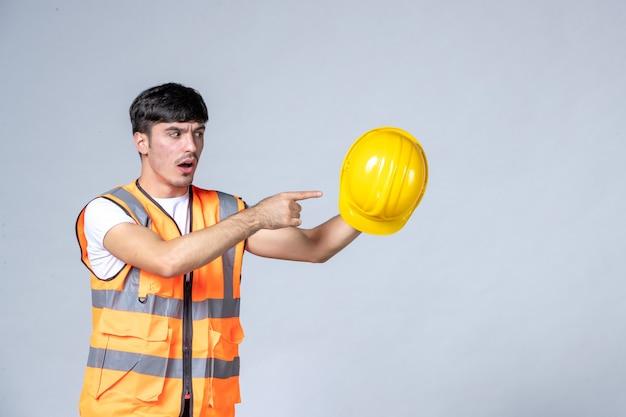 Vista frontal do construtor masculino de uniforme segurando um capacete amarelo na parede branca