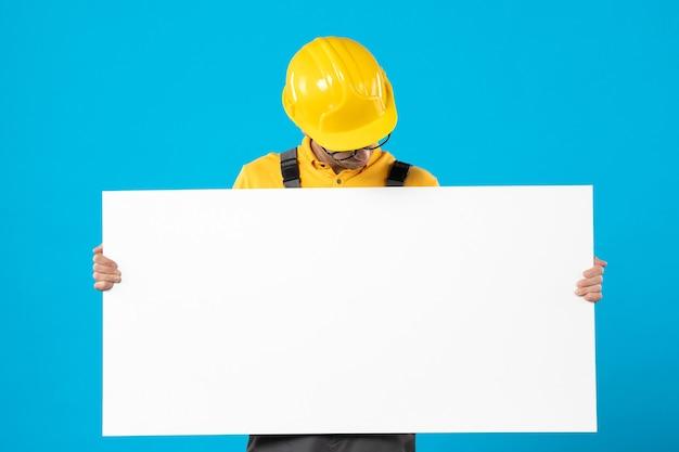 Vista frontal do construtor masculino em uniforme amarelo com plano de papel em azul