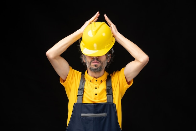 Vista frontal do construtor masculino em uniforme amarelo na parede preta