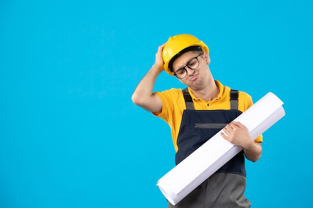 Vista frontal do construtor masculino estressado em uniforme amarelo com plano de papel em azul