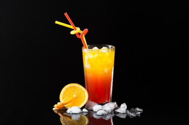 Vista frontal do copo de coquetel com cubos de gelo e laranja