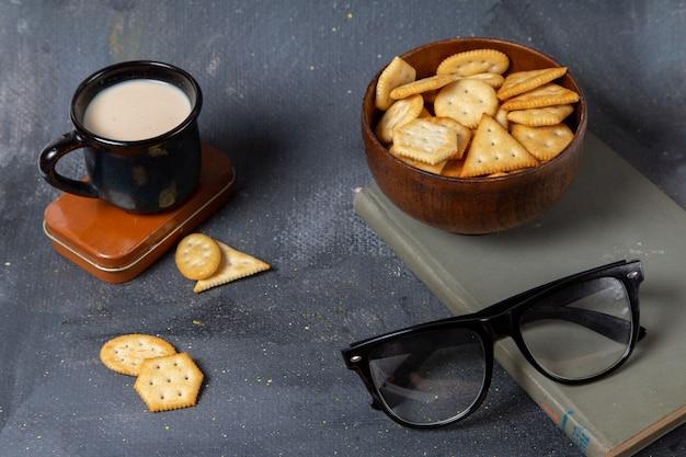 Vista frontal do copo de leite com biscoitos e óculos de sol na superfície cinza