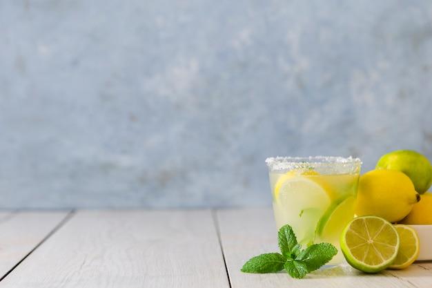 Vista frontal do copo de limonada com hortelã e frutas cítricas