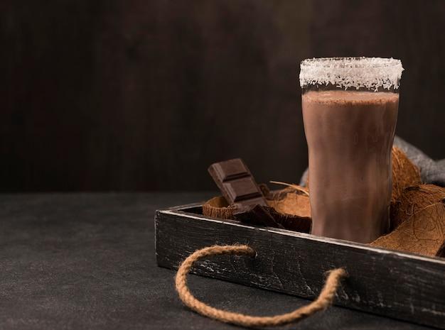 Vista frontal do copo de milk-shake na bandeja com chocolate e espaço de cópia