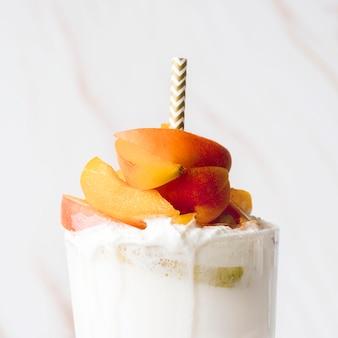 Vista frontal do copo de sobremesa com frutas e palha