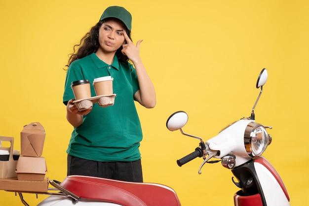 Vista frontal do correio feminino de uniforme verde com café sobre fundo amarelo serviço trabalhador trabalho trabalho comida mulher cor