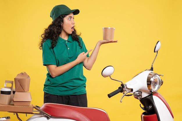 Vista frontal do correio feminino de uniforme verde com sobremesa no fundo amarelo cor de trabalho entrega de trabalho mulher serviço comida de trabalhador