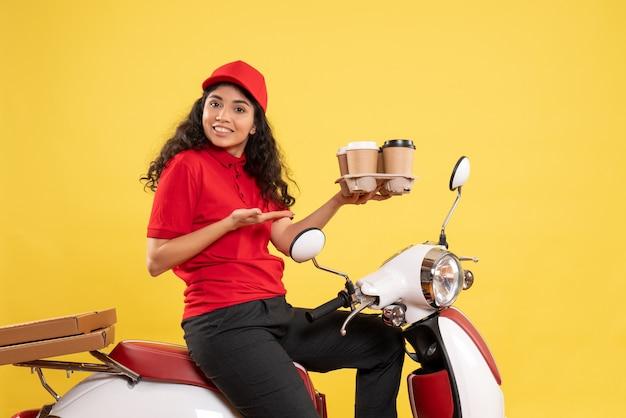 Vista frontal do correio feminino em bicicleta segurando xícaras de café no fundo amarelo trabalhador serviço uniforme trabalho mulher entrega trabalho