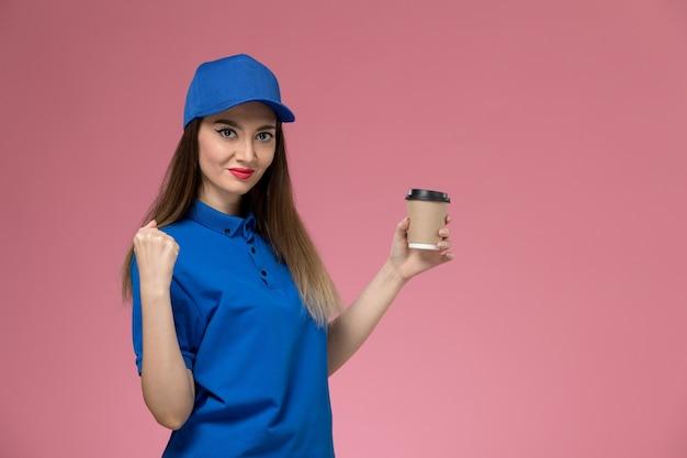 Vista frontal do correio feminino em uniforme azul e capa segurando a xícara de café de entrega na parede rosa trabalho menina mulher trabalhadora