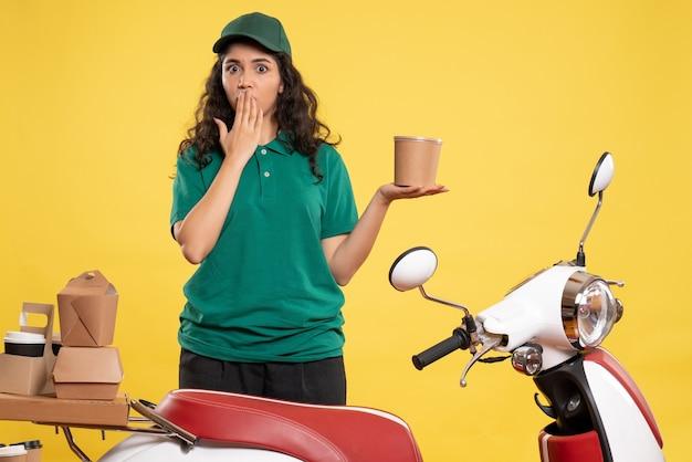 Vista frontal do correio feminino em uniforme verde com sobremesa em fundo amarelo cor de trabalho entrega de trabalho mulher comida de trabalhador