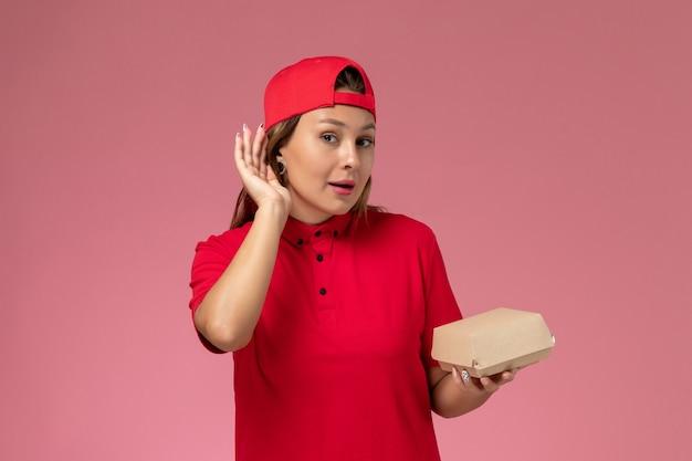 Vista frontal do correio feminino em uniforme vermelho e capa segurando pacote de comida de entrega em fundo rosa uniforme serviço de entrega empresa trabalho trabalhador trabalho