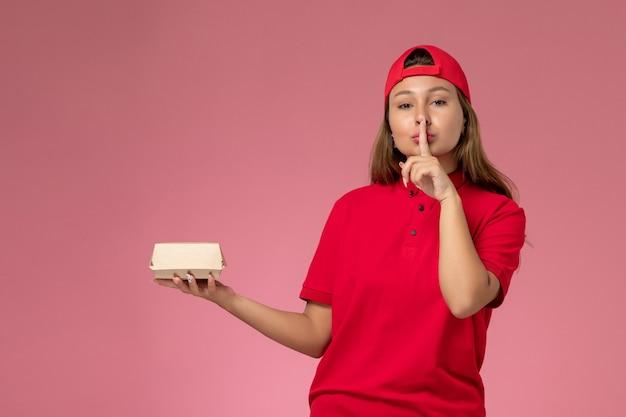 Vista frontal do correio feminino em uniforme vermelho e capa segurando pacote de entrega de comida em fundo rosa.