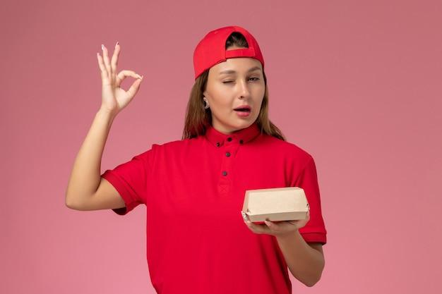 Vista frontal do correio feminino em uniforme vermelho e capa segurando pacote de entrega de comida no fundo rosa uniforme serviço de entrega empresa trabalho garota trabalhador