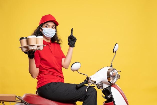 Vista frontal do correio feminino na máscara na bicicleta com xícaras de café no fundo amarelo trabalhador serviço pandemia uniforme trabalho mulher entrega covid-
