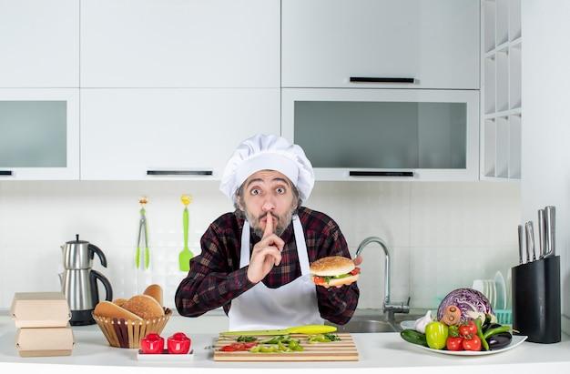 Vista frontal do cozinheiro segurando hambúrguer e fazendo sinal de silêncio em pé atrás da mesa da cozinha