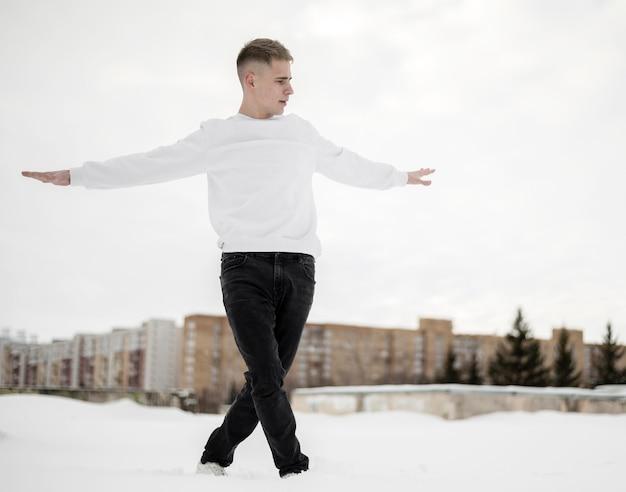 Vista frontal do dançarino de hip-hop bonito posando do lado de fora