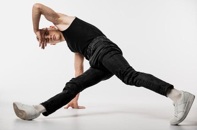 Vista frontal do dançarino em jeans e regata dançando