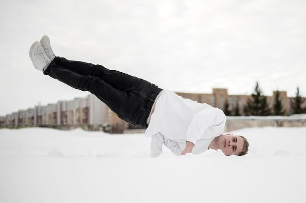 Vista frontal do dançarino equilibrando seu corpo com uma mão