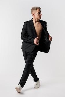 Vista frontal do dançarino masculino de terno e tênis posando com blazer aberto