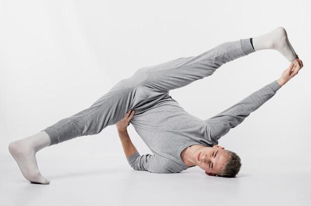 Vista frontal do dançarino masculino em agasalho e meias posando com um movimento de dança